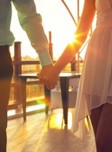 fashion outdoor photo of woman and man in elegant clothes,holding by hands and posing on sunset in restaurant